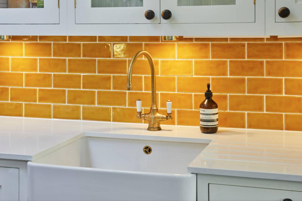 Kitchen worktop with orange metro tile backsplash by Holland Street Kitchens