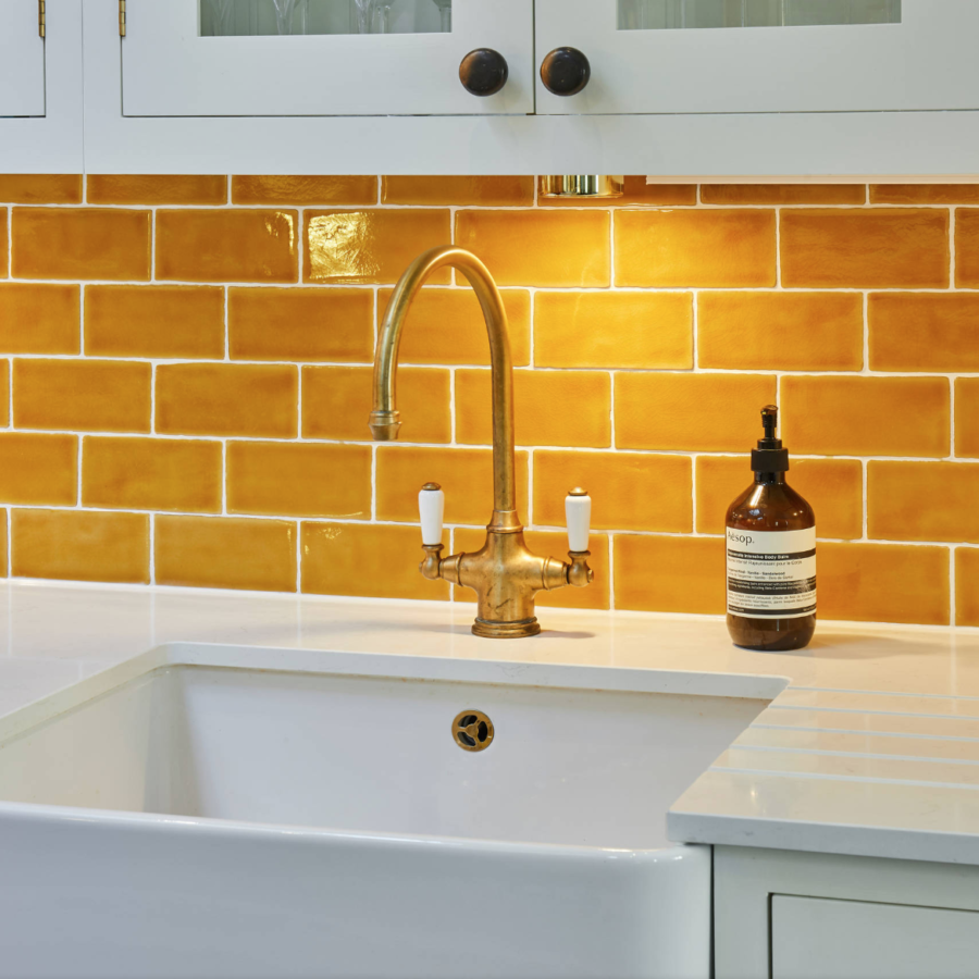 Kitchen worktop with orange metro tile backsplash by Holland Street Kitchens